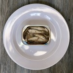 An open can of Beach Cliff Sardines in water on a round white plate.
