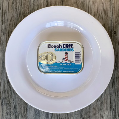 An unopened can of Beach Cliff Sardines in water on a round white plate. The table they're on is made of wood.