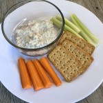 A plate of crackers, carrots and celery sticks, with a small bowl of a dill and mayo dip incorporating Beach Cliff Sardines in Water.
