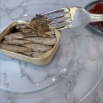 A closeup of Bumble Bee wild sardines on the tines of a fork.