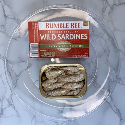 An open can of Bumble Bee wild sardines next to their box on a clear plate.