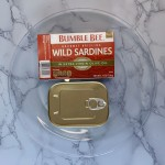 A closed can of Bumble Bee wild sardines next to their box on a clear plate.