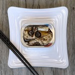 An opened can of Chicken of the Sea Mediterranean style sardines on a square white plate. Black olives are visible on top of the fish, and chopsticks sit diagonally on the corner of the plate.