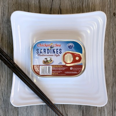 An unopened can of Chicken of the Sea Mediterranean style sardines on a square white plate. Chopsticks sit diagonally on the corner of the plate.