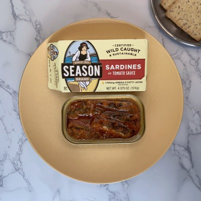 An open can of Season sardines in tomato sauce next to their box on a yellow plate.