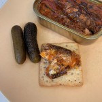 A chunk of Season sardines in tomato sauce on a rectangular cracker next to two small pickles.