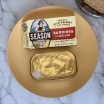 An unopened can of Season sardines in tomato sauce next to their box on a yellow plate.